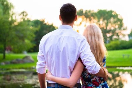 to tight: Couple dreaming their life together looking in romantic sunset, man embracing his girlfriend
