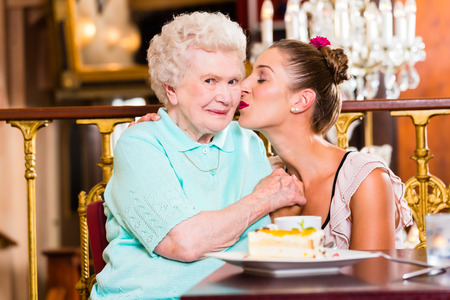 Senior woman and granddaughter with cake in old fashioned cafe photo