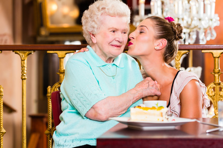 old fashioned: Senior woman and granddaughter with cake in old fashioned cafe