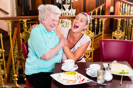 Senior woman and granddaughter laughing having fun with coffee and cake in cafe photo