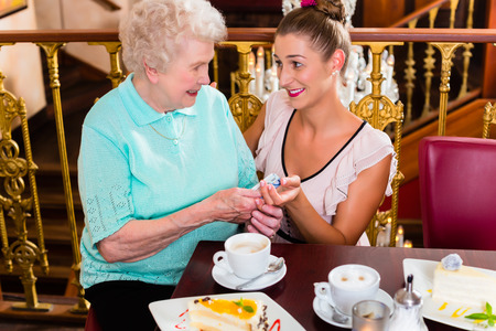 Senior woman and granddaughter drinking coffee and eating cake in cafe photo