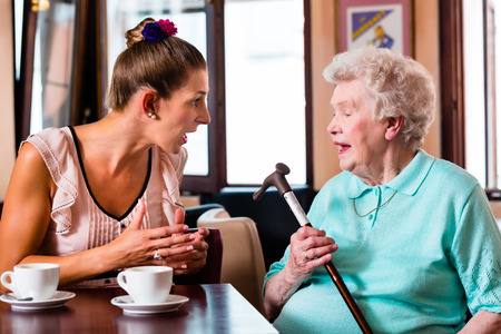 argument: Grandmother and granddaughter having argument in cafe, the senior woman in threatening with her crutch