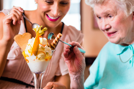 woman with ice cream: Senior woman and granddaughter having fun eating ice cream sundae in cafe Stock Photo