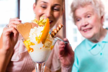 comiendo helado: Mujer mayor y su nieta se divierten comiendo helado sundae en la cafeter�a