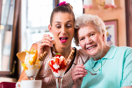 Senior woman and granddaughter having fun eating ice cream sundae in cafe photo