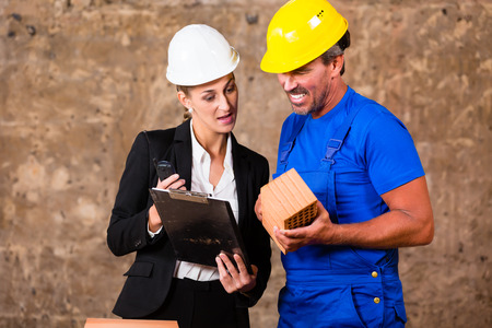 construction material: Architect and builder on construction site discussing brick and material