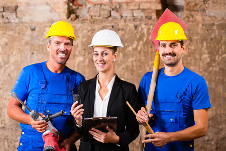 machines: Builders with machines and architect on construction site Stock Photo