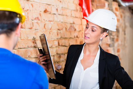 acceptance: Worker and architect at acceptance on construction site Stock Photo
