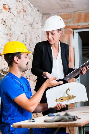 interior designer: Construction worker and interior designer with door handle discussing door handles Stock Photo