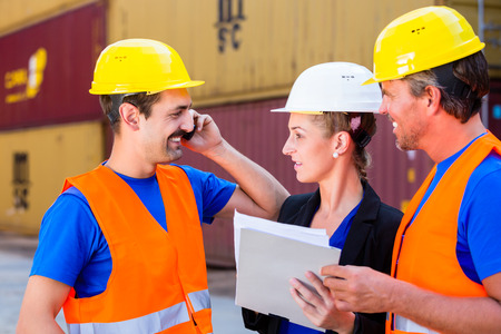 empleada domestica: Trabajador y gerente de la empresa de envío de discutir los documentos de transporte o envío, un hombre está utilizando teléfono o walkie-talkie Foto de archivo