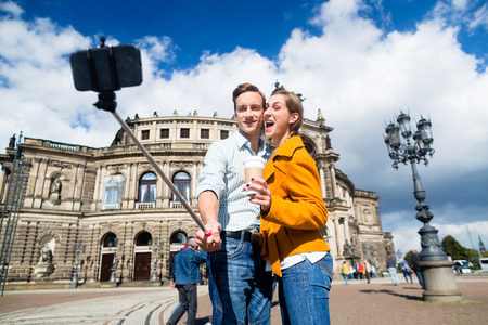 to stick: Tourist couple at Semperoper in Dresden taking selfie with phone on stick