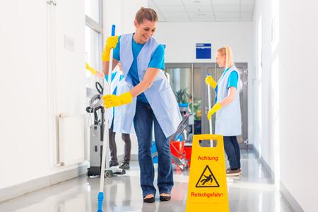 cleaning team: Comercial de trabajo de la brigada de limpieza fregar el suelo