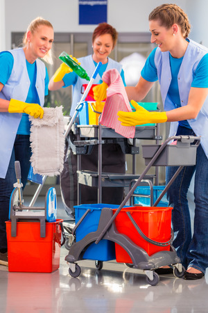 cleaning crew: Commercial cleaners doing the job together, three women with trolley working