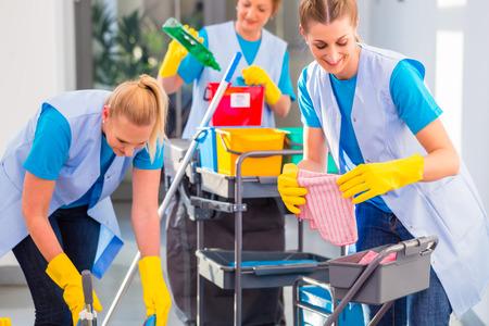 personal de limpieza: Limpiadores comerciales que hacen el trabajo en conjunto, tres mujeres con trabajo carro Foto de archivo