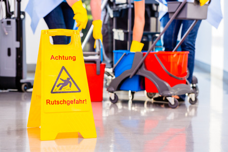 mujer limpiando: Se�al de peligro en planta en operaci�n de limpieza