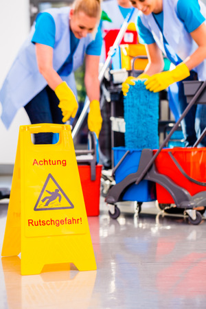 charwoman: Warning sign on floor in cleaning operation Stock Photo