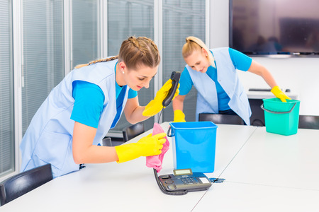 cleaning an office: Commercial cleaning crew ladies working as team in office