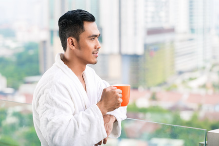 waking up: Asian man in morning front of city skyline drinking coffee