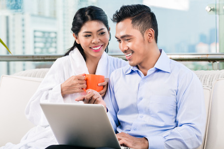 Businessman working in home office as telecommuter, his wife is bringing coffee photo