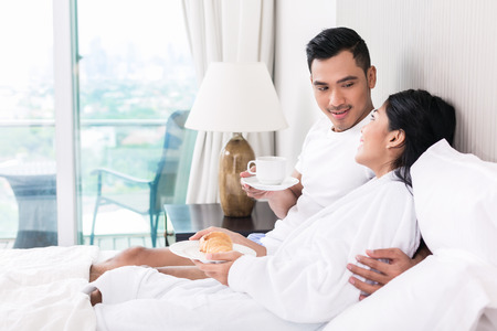 breakfast in bed: Asian couple lounging in bed at morning Stock Photo