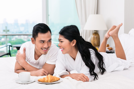 apartment: Asian couple having breakfast in bed with croissant and coffee