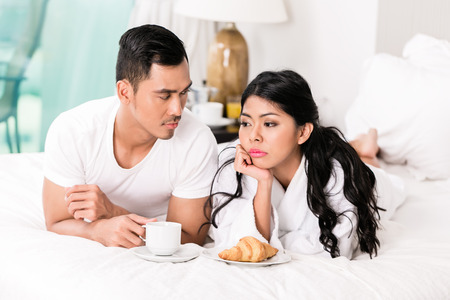 breakfast in bed: Marital issues - asian man feeling rejected by his wife, they are laying in bed
