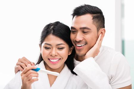 prueba de embarazo: Mujer asi�tica sorprendiendo a su marido con la prueba de embarazo positiva, parece razonablemente satisfechos Foto de archivo