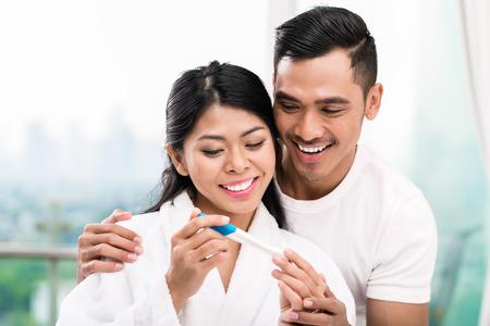 pareja en la cama: Mujer asiática sorprendiendo a su marido con la prueba de embarazo positiva, parece razonablemente satisfechos Foto de archivo