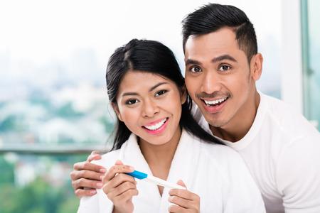 marido y mujer: Mujer asi�tica sorprendiendo a su marido con la prueba de embarazo positiva, parece razonablemente satisfechos Foto de archivo