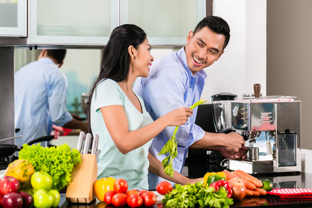 indonesian food: Asian couple, man and woman, cooking food together in kitchen and making coffee