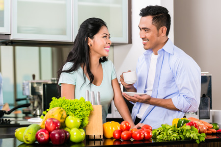 Asian couple, man and woman, cooking food together in kitchen and making coffee photo