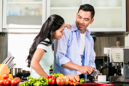 preparing food: Asian couple, man and woman, cooking food together in kitchen and making coffee