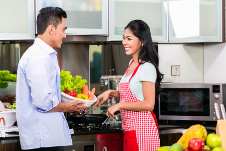 asian wife: Asian man and woman cooking together in kitchen preparing dinner