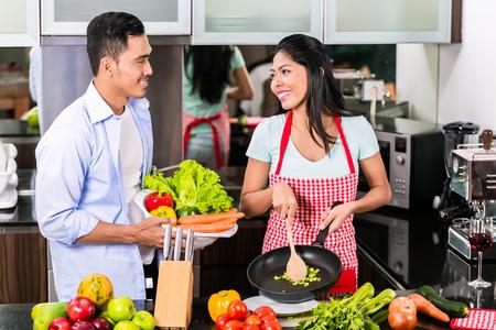 pareja casa: Hombre asi�tico y una mujer cocinar juntos en la cocina preparando la cena
