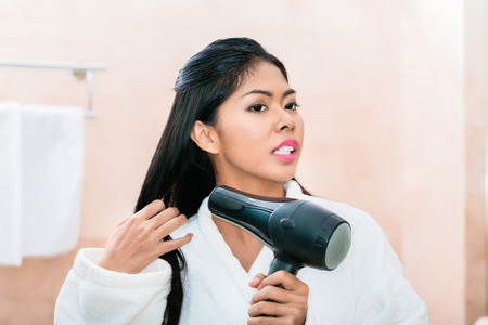 hair drier: Asian woman in bathroom drying hair with blow dryer