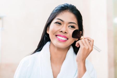 mujer maquillandose: Mujer asiática en la aplicación de maquillaje en frente del espejo del baño Foto de archivo