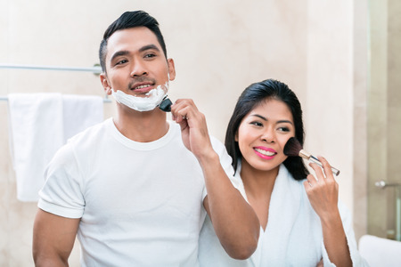 Asian morning couple, man and woman, in bathroom with makeup and shaver Stock Photo