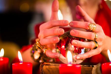 esoterismo: Fortuneteller Mujer o esotérica Oracle, ve en el futuro mirando en su bola de cristal durante una sesión de espiritismo para interpretarlos y para responder a las preguntas Foto de archivo