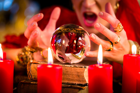 esoterismo: Fortuneteller Mujer o esot�rica Oracle, ve en el futuro mirando en su bola de cristal durante una sesi�n de espiritismo para interpretarlos y para responder a las preguntas Foto de archivo