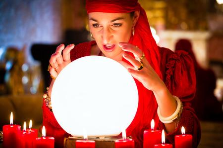 adivino: Fortuneteller Mujer o esot�rica Oracle, ve en el futuro mirando en su bola de cristal durante una sesi�n de espiritismo para interpretarlos y para responder a las preguntas Foto de archivo