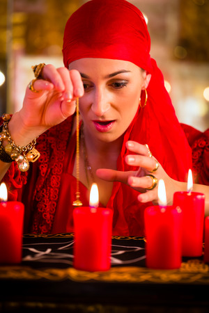 Female Fortuneteller or esoteric Oracle, sees in the future by dowsing her pendulum during a Seance to interpret them and to answer questions photo