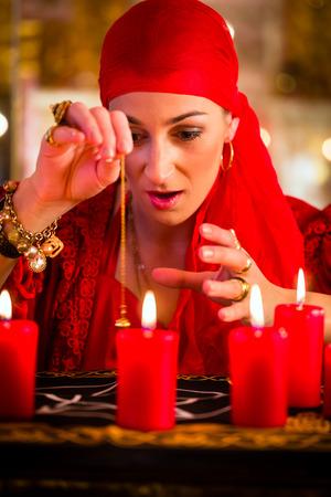 soothsayer: Fortuneteller Mujer o esotérica Oracle, ve en el futuro por su radiestesia péndulo durante una sesión de espiritismo para interpretarlas y responder preguntas