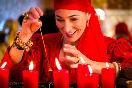 adivino: Fortuneteller Mujer o esotérica Oracle, ve en el futuro por su radiestesia péndulo durante una sesión de espiritismo para interpretarlas y responder preguntas