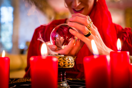 Fortuneteller or esoteric Oracle, sees in the future by looking into their crystal ball, incense burning and candles giving light photo