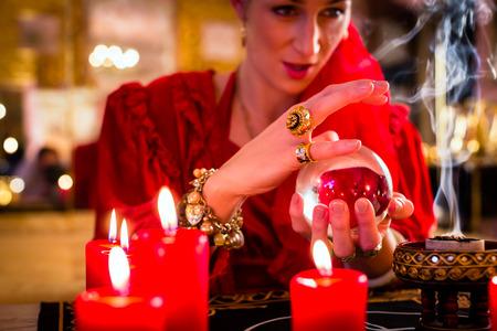soothsayer: Adivino o esotérica Oracle, ve en el futuro mirando en su bola de cristal, la quema de incienso y velas dando luz
