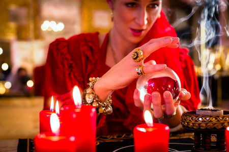 fortuneteller: Fortuneteller or esoteric Oracle, sees in the future by looking into their crystal ball, incense burning and candles giving light Stock Photo