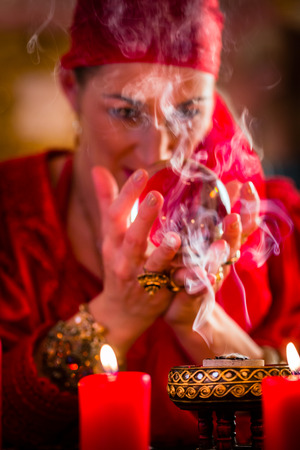 esotericism: Fortuneteller or esoteric Oracle, sees in the future by looking into their crystal ball, incense burning and candles giving light Stock Photo