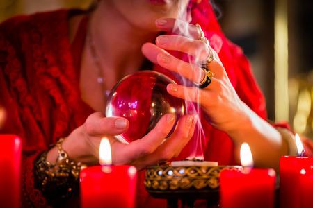 incienso: Adivino o esotérica Oracle, ve en el futuro mirando en su bola de cristal, la quema de incienso y velas dando luz