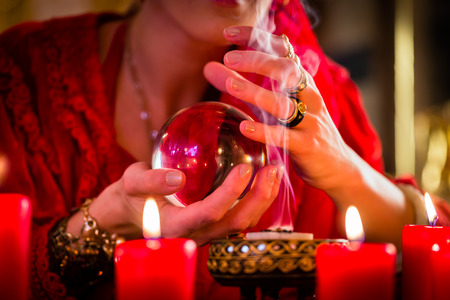 esot�risme: Fortuneteller ou �sot�rique Oracle, voit dans l'avenir en regardant dans leur boule de cristal, br�ler de l'encens et des bougies donnant la lumi�re Banque d'images