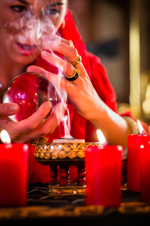 to foresee: Fortuneteller or esoteric Oracle, sees in the future by looking into their crystal ball, incense burning and candles giving light Stock Photo